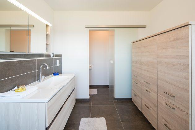 Moderner Komfort: das Badezimmer im Obergeschoss bietet genügend Stauraum. (Foto: FingerHaus)