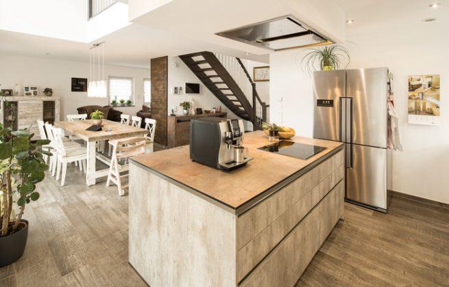 Die Kücheninsel bietet genügend Platz gemeinsamen Kochen oder für einen Espresso zwischendurch. Außerdem ist die Kommunikation zum Esstisch möglich. (Foto: FingerHaus)