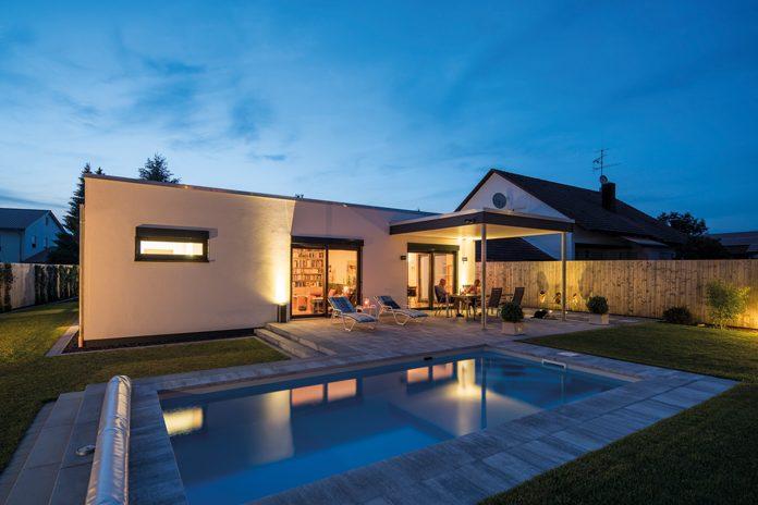 Bungalow NIVO - Modernes Haus zur blauen Stunde: Auf ihren professionell gestalteten Garten ist die Baufamilie sehr stolz. Der Pool wird oft und gern genutzt. (Foto: FingerHaus)