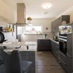 Wie an der Fassade finden sich auch im Inneren des Hauses Kontraste in Weiß und Anthrazit, hier in der offenen Küche des Wohnbereichs. (Foto: FingerHaus)