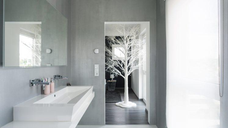 Effektvoll: Das Bad grenzt direkt an das Schlafzimmer. Die hellgrau schimmernde Farbe haben die Hausbesitzer selbst gestrichen. (Foto: FingerHaus)