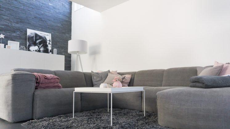 Selbst gefertigt: Kissen und Decken machen die Sofaecke gemütlich. Die Steinwand zieht sich hinauf bis ins Obergeschoss. (Foto: FingerHaus)