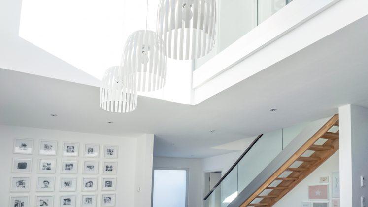 Luftig: Um eine zweite Galerie zu schaffen, verzichteten die Bauherren auf das zweite Bad. Das Geländer oben ist das gleiche wie an der Holztreppe. (Foto: FingerHaus)