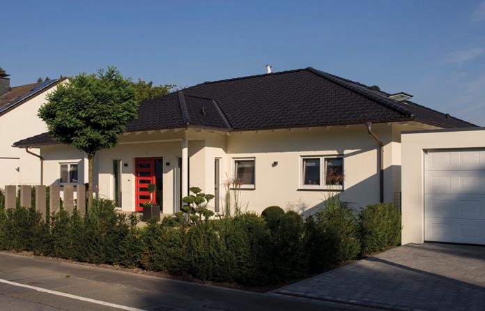 Frei geplanter Bungalow: Das Haus mit dem schicken Eingangsportal fällt auf. Zu beiden Seiten steht eine Doppelgarage. In einer davon parken die beiden Oldtimer des Hausherrn. (Foto: FingerHaus)
