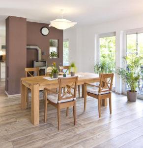 Diese gemütliche Essecke haben die Baumanns ins Herz geschlossen: Am großen Holztisch vor dem gemütlichen Ofen spielt sich das kunterbunte Familienleben ab. (Foto: FingerHaus)