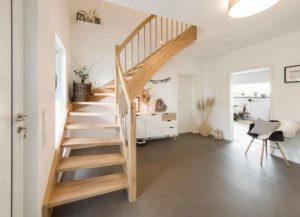 Diele: Die L-förmige Treppe nimmt wenig Platz in Anspruch. Hier im Eingangsbereich verlegten die Hofmanns extrarobuste Holzfliesen: wasserdicht, fußwarm und schlagfest. In der Kommode lagern Schuhe. (Foto: FingerHaus)