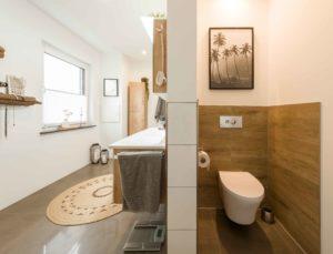 Großes Badezimmer: Die Holzoptik der Wandfliesen greift die Brauntöne im Raum auf. Zum Beispiel die alten Balken, die Svenja und Normen Hofmann zu Ablagen umbauten. Gegenüber dem WC verschwindet auch die Dusche hinter einer T-Wand. (Foto: FingerHaus)